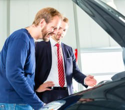 Seller or car salesman and client or customer in car dealership
