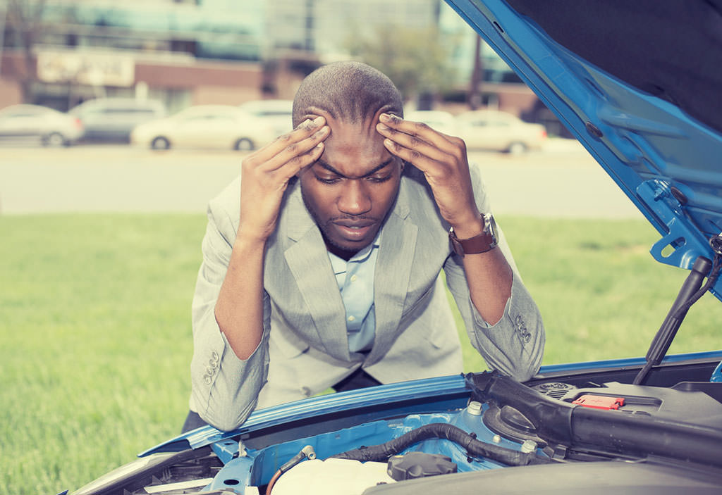 young stressed man having trouble with his broken car